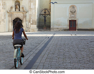 Cycling - Brunette woman riding a bicycle in an old city...