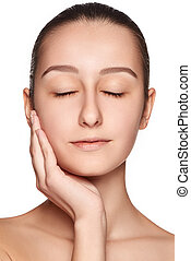 Portrait of beautiful girl stroking her face with healthy...