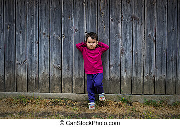 Summer portrait of a cute little girl of two years old by the fence