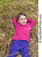 Portrait of a little girl smiling as she lies in  the grass