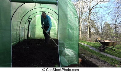 man level soil greenhouse - Farmer gardener man leveling...