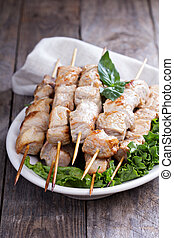 Pork kebabs with fresh salad leaves on a table