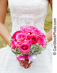 bridal bouquet of roses in hands of the bride