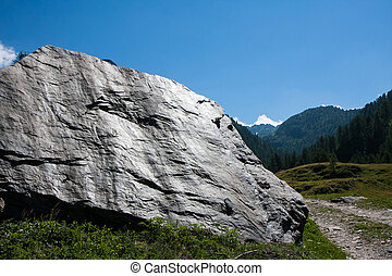 mountain landscape with a large boulder in the foreground