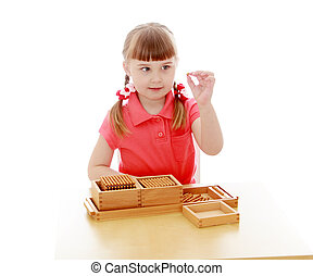 The girl in the Montessori environment, studying the...