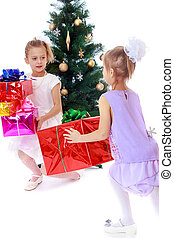 Girls sisters around the Christmas tree fuss considering...