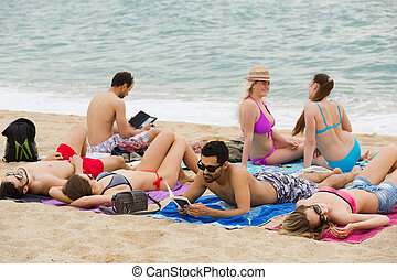 people laying on sand at beach