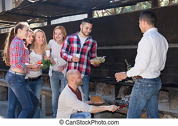 Friends frying meat outdoors - Group of friends frying a...