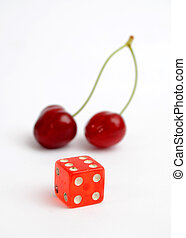 Red dice in front of ripe cherries - Picture of a Red dice...