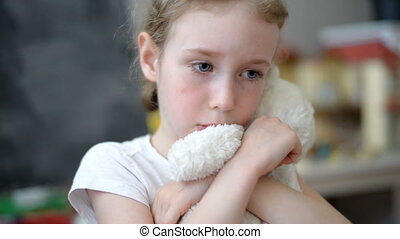 Sad little girl with teddy bear.