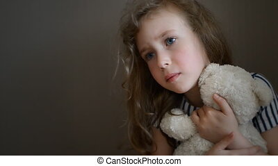 Sad little girl with bear.