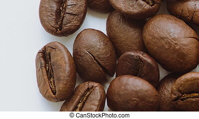 A pile of roasted coffee beans rotating Close up