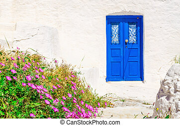 Blue wooden door, white wall and flowers, Greece - Iconic...