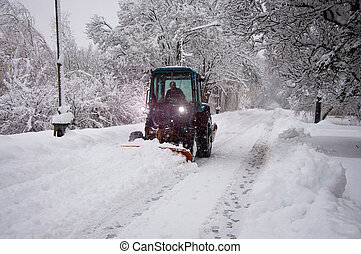 Tractor cleans snow on the road