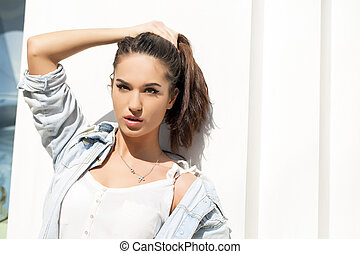 Young woman against white wall