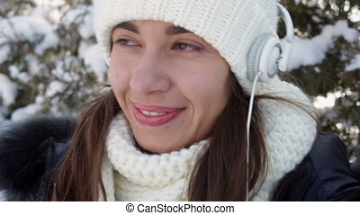 beautiful woman listening to music with headphones in the...
