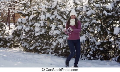 young woman in a white hat throwing snowballs