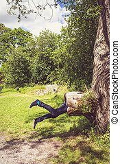 Young man looks like he is being eaten by a big tree in the park.