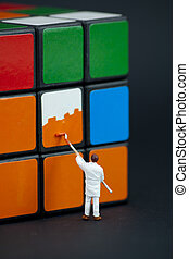 Man painting the squares on a rubiks cube - Man painting the...