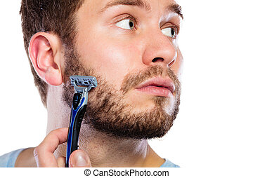Young man with beard holding razor blade - Health beauty and...