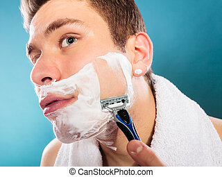 Handsome man shaving with razor - Health beauty and skin...