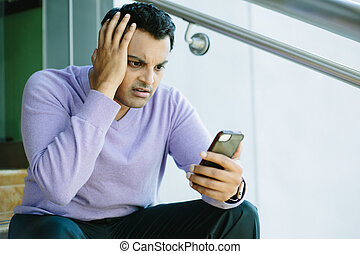 Man looking at bad news on cellphone - Closeup portrait,...