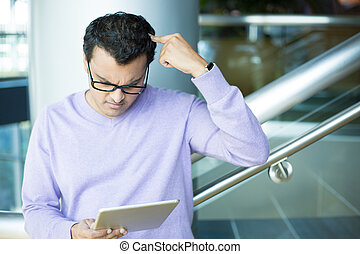 Man confused by what he sees on tablet - Closeup portrait,...