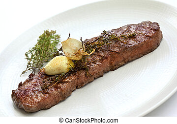 Beef steak, garlic and thyme on a plate
