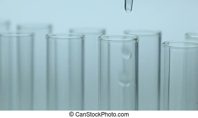 Liquid dripping into test tube - Liquid dripping from...