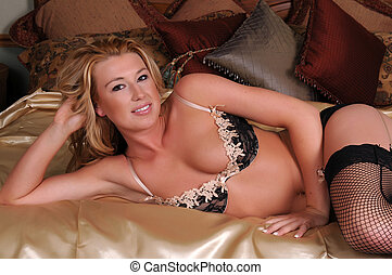 Blonde - Statuesque blonde woman in lacy lingerie lying in...