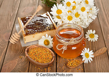 Honey, chamomile and pollen on a brown background