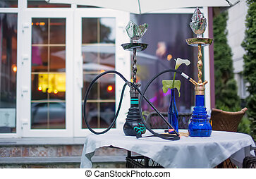 Close-up photo of two hookahs on table