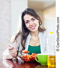 woman eating veggie salad with spoon