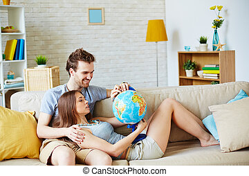 Couple with globe - Happy young man and woman with globe...