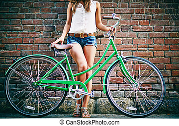 Urban sport - Active female with bicycle standing by brick...