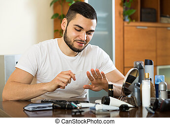 man using nail file - Handsome european man using nail file
