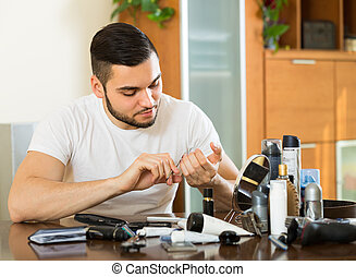 Man doing manicure at home - Handsome young smiling...