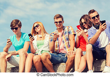 group of smiling friends with smartphones outdoors -...
