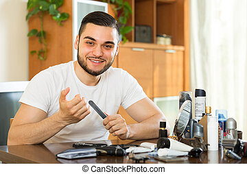 Young guy cutting nails - Young guy cutting nails with...