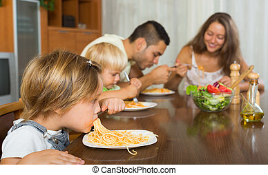 family of four  having lunch with pasta together