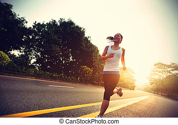Runner athlete running at road woman fitness sunrise jogging...