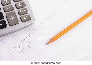 math - calculation concept with pencil and notebook, focus...