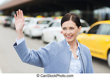 smiling young woman with waving hand over taxi - travel,...