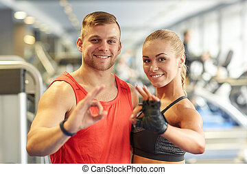 smiling man and woman showing ok hand sign in gym - sport,...