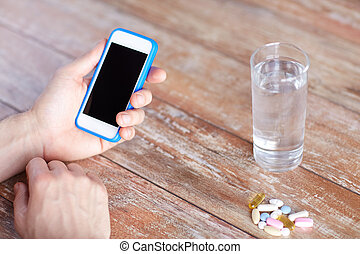 close up of hands with smartphone, pills and water -...