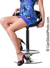 Legs of a beautiful woman sitting on a chair.