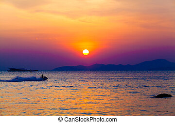 the jetski above the water at sunset. Silhouette of people...