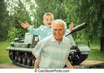 Grandfather and grandson are photographed on a background of...
