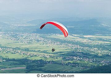 Paragliding over village - Paraglider flying over village in...