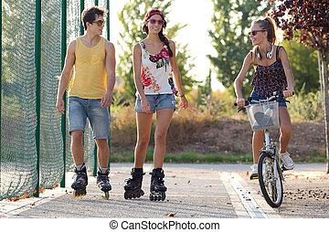 Group of friends with roller skates and bike riding in the...
